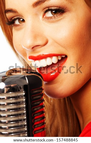 Close up portrait of a beautiful young female vocalist wearing bright red lipstick singing into a microphone - stock photo