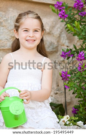 Close up portrait of a beautiful young girl child sitting in a holiday home garden holding a small watering can and smiling joyfully during  a sunny day. Childhood summer vacation lifestyle, outdoors. - stock photo