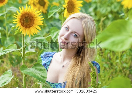 Close up portrait of a beautiful young girl in blue dress on a background field of sunflowers - stock photo