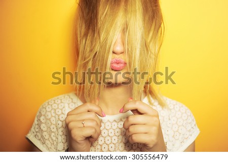 close-up portrait of a beautiful young girl sexy hipster on a yellow background is bright and smiling and posing in white blouse and hair in the tail  with manicure and pink lips - stock photo