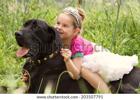 Close up portrait of a beautiful young girl wearing a fancy dress, sitting on her dog pet back, smiling and enjoying a summer holiday. Active family with pets outdoors lifestyle. - stock photo