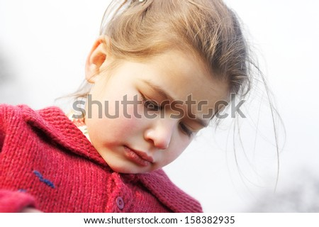 Close up portrait of a beautiful young girl with an unhappy and upset expression, wearing a red jumper against the sky during a sunny winter autumn day outdoors. - stock photo