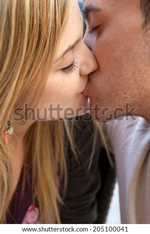 Close up portrait of a beautiful young girlfriend and boyfriend in love, innocently kissing with their eyes shut. Couple relationships feelings and emotions, outdoors. - stock photo