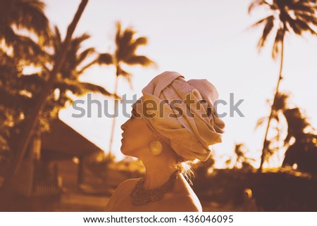close-up portrait of a beautiful young sensual sexy woman with a turban on his head and African ornaments  full lips and expressive eyes on a sunny day at sunset in the tropical hot jungle in Thailand - stock photo