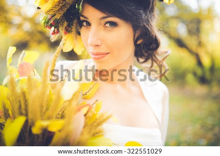close-up portrait of a beautiful young sexy girl brunette bride with flowers in her hair look attractive in a white dress on a background of autumn forest and leaves posing and smiling