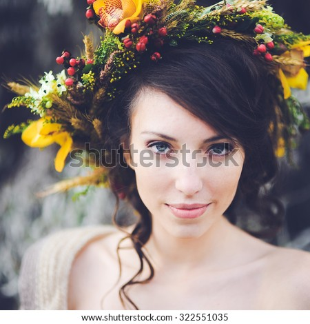 close-up portrait of a beautiful young sexy girl brunette bride with flowers in her hair look attractive in a white dress on a background of autumn forest and leaves posing and smiling - stock photo