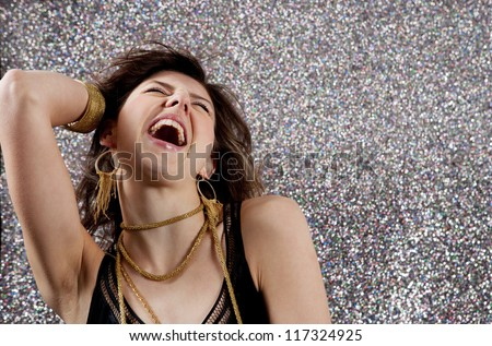 Close up portrait of a beautiful young woman dancing and singing at a party against a silver glitter background. - stock photo