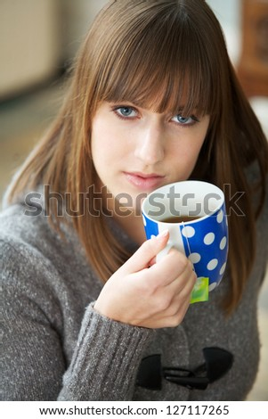 Close up portrait of a beautiful young woman drinking coffee - stock photo