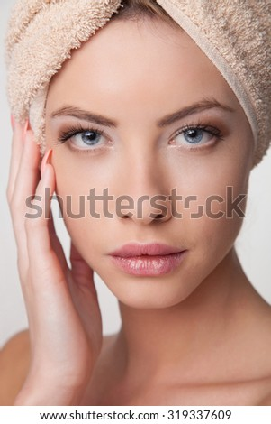 Close-up portrait of a beautiful young woman holding hands by her face and looking at camera. - stock photo
