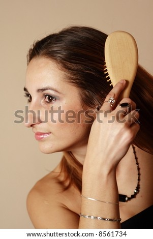Close-up Portrait of a Beautiful Young Woman in studio, brushing her hair