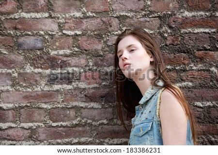 Close up portrait of a beautiful young woman leaning against brick wall outdoors