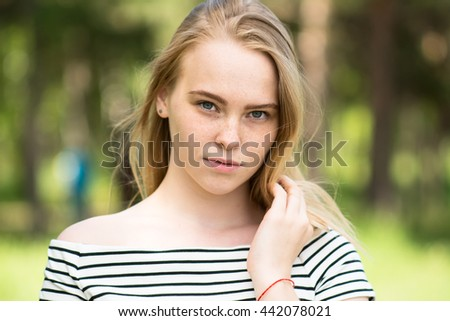 Close-up portrait of a beautiful young woman looking into the camera. A woman in a striped dress on a background of blurred trees - stock photo