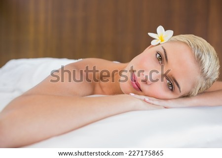 Close up portrait of a beautiful young woman lying on massage table at spa center - stock photo