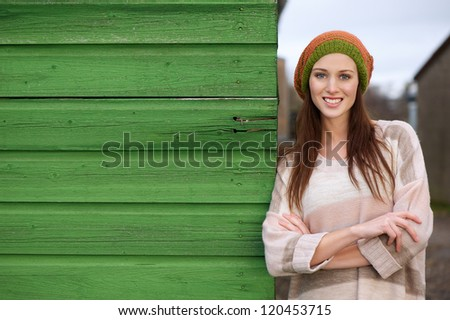 Close up portrait of a beautiful young woman smiling and  leaning against a green wooden wall outdoors. Possible for copy space - stock photo