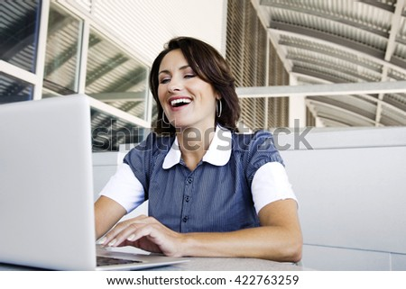 Close up portrait of a beautiful young woman smiling and looking at laptop screen - stock photo