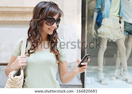 Close up portrait of a beautiful young woman standing by a fashion store window display with manikins, holding and using a smartphone while smiling outdoors.