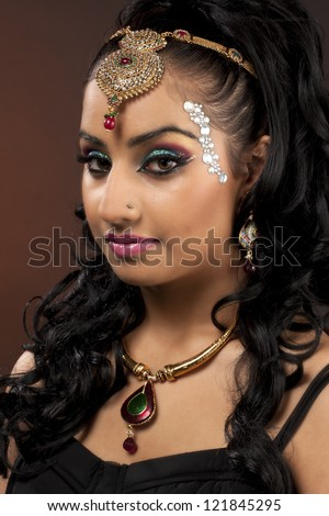 Close-up portrait of a beautiful young woman wearing make-up and jewelry