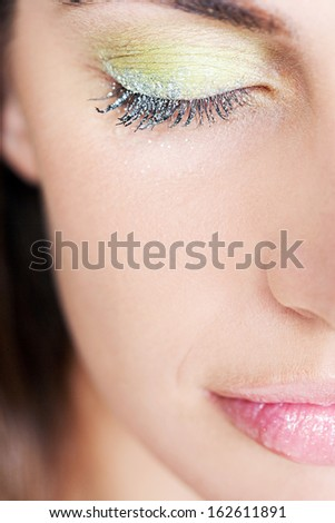 Close up portrait of a beautiful young woman wearing party eyeshadow make up and glitter mascara on her eyelashes with her eyes shut, calm and tranquil. - stock photo