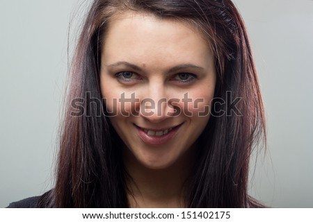 Close up portrait of a beautiful young woman with an isolated grey background. - stock photo