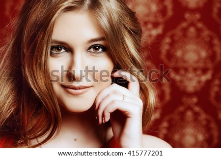Close-up portrait of a beautiful young woman with magnificent wavy hair and evening make-up smiling at camera.  - stock photo