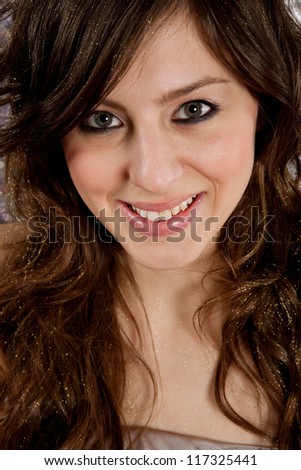 Close up portrait of a beautiful young woman with party make up on and glitter on her hair, smiling.