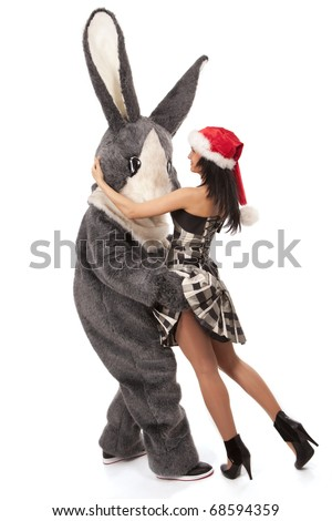 Close-up portrait of a big grey fur's color rabbit flirting with cute girl and keeps trying to get under her skirt. - stock photo