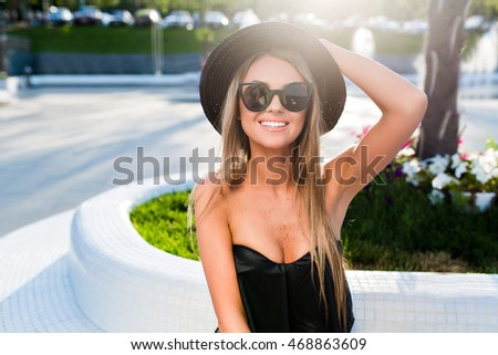 Close-up portrait of a blond girl with long hair posing in park. She wears black sunglasses, hat, T-shirt. She holds her hat and smiling to the camera.