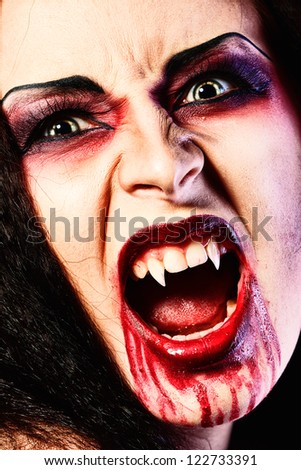 Close-up portrait of a bloodthirsty female vampire. - stock photo