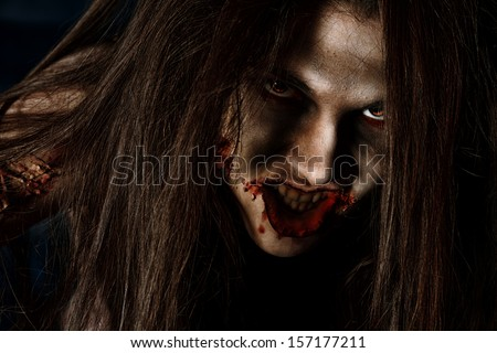 Close-up portrait of a bloodthirsty gnarling zombi. - stock photo