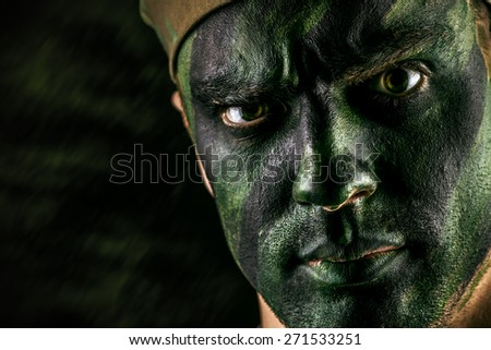 Close-up portrait of a brave soldier in war paint looking at camera. Black background. Military, war. Special forces. - stock photo