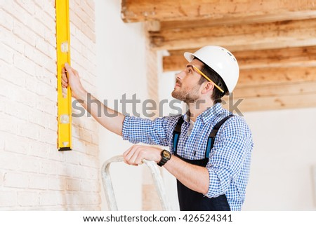 Close-up portrait of a builder holding construction level against the wall and standing on the ladder indoors - stock photo