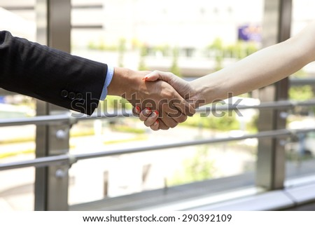 Close up portrait of a businessman and a businesswoman shaking hands in - stock photo