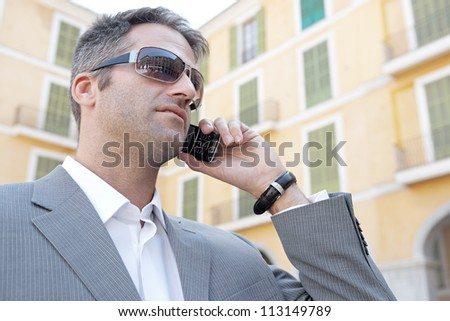 Close up portrait of a businessman having a phone conversation using his smart phone while standing in front of a classic building in the city. - stock photo