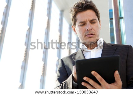 Close up portrait of a businessman standing by a modern architecture glass office building in the city, using a digital technology smart tablet pad.