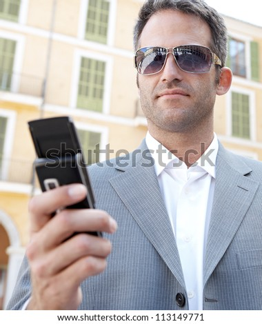 Close up portrait of a businessman using his smart phone while standing in front of a classic office building in the city. - stock photo