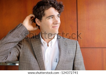 Close up portrait of a businessman wearing an elegant suit and scratching his head while standing against a luxurious wooden wall, looking away. - stock photo
