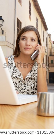 Close up portrait of a businesswoman using a cell phone and a laptop computer while sitting down at a coffee shop table outdoors.