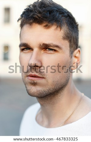 Close-up portrait of a Casual handsome man with a beard looking at camera, outdoors