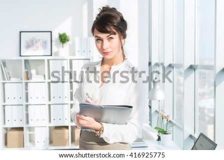 Close-up portrait of a caucasian female office assistant at her workplace. Confident clerk, standing, holding document folder. - stock photo