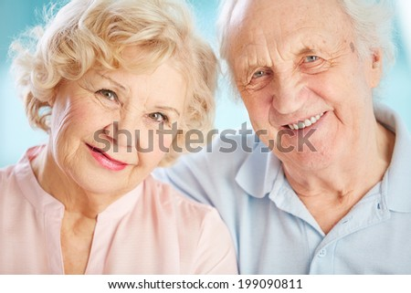 Close-up portrait of a charming elder couple looking at the viewer with a smile - stock photo