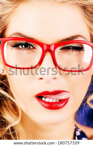 Close-up portrait of a charming pin-up woman with red lips and reg glasses. - stock photo