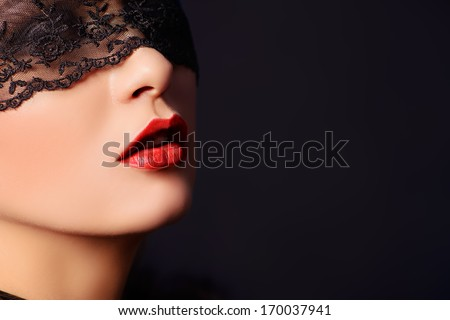 Close-up portrait of a charming  woman in black lace mask. - stock photo