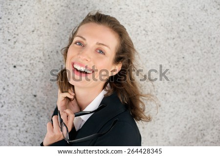 Close up portrait of a cheerful business woman laughing with glasses - stock photo