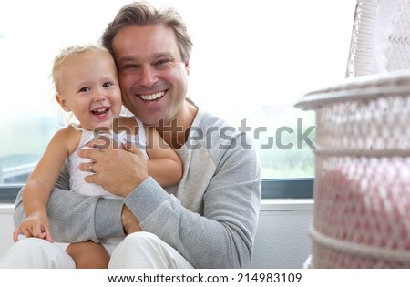 Close up portrait of a cheerful father with cute baby laughing together - stock photo
