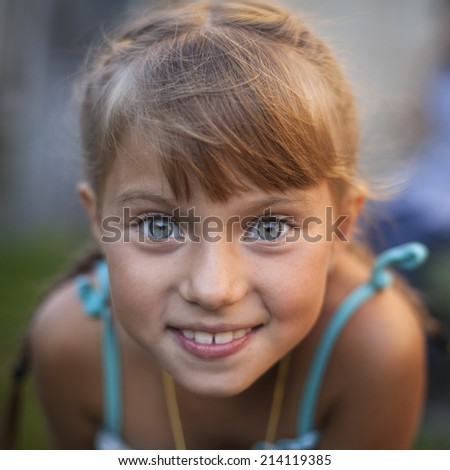 Close-up portrait of a cheerful little cute girl. - stock photo