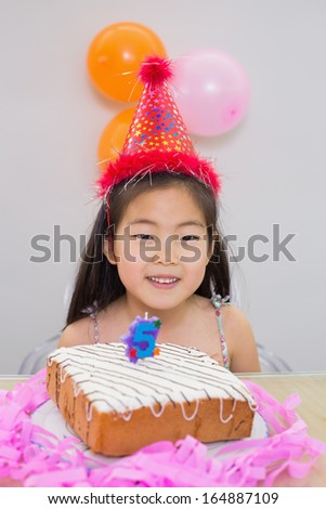 Close-up portrait of a cheerful little girl at her birthday party - stock photo