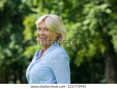 Close up portrait of a cheerful older woman smiling outdoors - stock photo