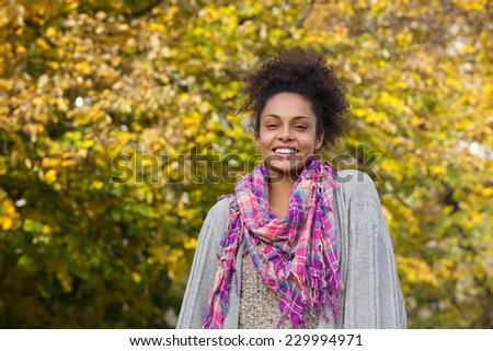 Close up portrait of a cheerful young african american woman standing outdoors in autumn - stock photo