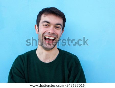Close up portrait of a cheerful young man laughing against blue background - stock photo