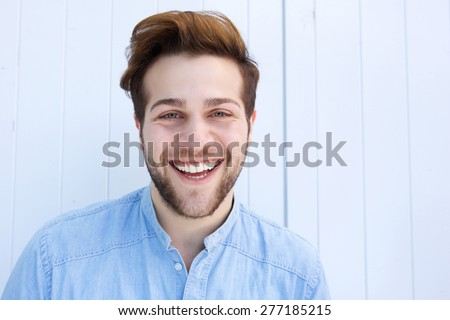 Close up portrait of a cheerful young man laughing against white background - stock photo